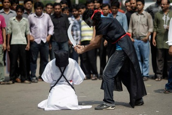 Members of Magic Movement, a group of young Bangladeshis, stage a mock execution scene in protest of Saudi Arabia beheading of eight Bangladeshi workers in front of National Museum in Dhaka October 15, 2011. Eight Bangladeshi migrants have been beheaded in the Saudi Arabian capital Riyadh in public on October 7, as they were sentenced to death for the alleged murder of an Egyptian man in April 2007, an interior ministry of Saudua Arabia statement said. REUTERS/Andrew Biraj (BANGLADESH - Tags: POLITICS CRIME LAW) - RTXXS1D