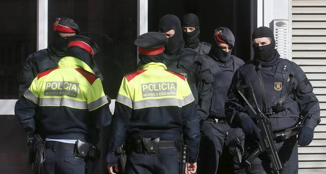 Catalan police officers stand guard outside a block of flats in Sabadell during an operation against Islamist militants